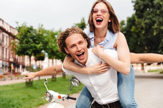 Freudiges junges paar, das spaß zusammen mit roller hat und in die kamera schaut, während es im park ist