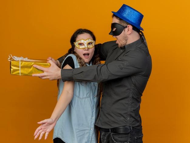 Freudiges junges partypaar, das maskerade-eue-masken-kerl trägt, der geschenkbox hinter mädchen lokalisiert auf orange hält