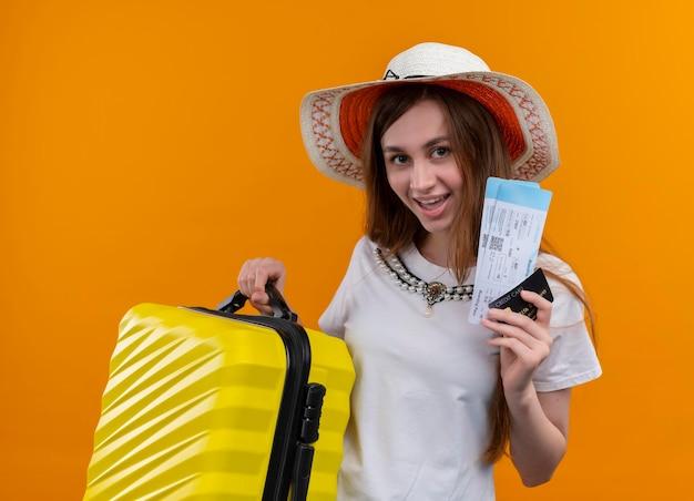 Freudiges junges reisendes mädchen, das hut hält, der koffer und flugtickets, kreditkarte auf lokalisiertem orangefarbenem raum hält