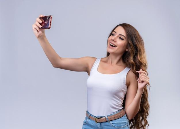 Freudiges junges schönes mädchen, das selfie nimmt