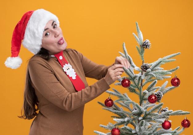 Freudiges junges schönes mädchen, das weihnachtshut mit krawatte trägt, die nahe weihnachtsbaum steht, der zunge lokalisiert auf orange hintergrund zeigt