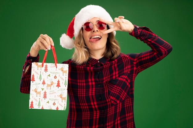 Freudiges junges schönes mädchen, das weihnachtsmütze mit brille hält, die geschenktüte hält, die zunge mit friedensgeste lokalisiert auf grünem hintergrund zeigt