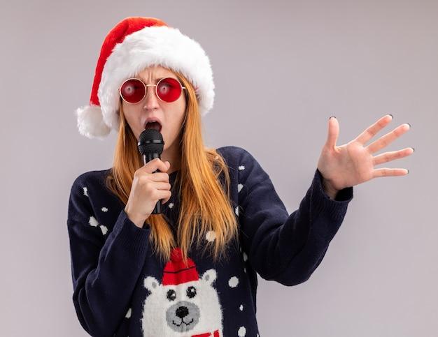 Freudiges junges schönes mädchen, das weihnachtsmütze und brille singend singend auf mikrofonverbreitungshand lokalisiert auf weißem hintergrund trägt