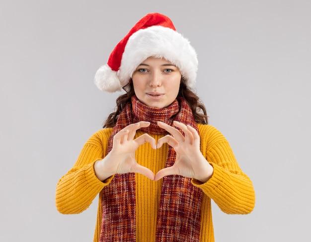 Freudiges junges slawisches mädchen mit weihnachtsmütze und mit schal um hals, der herzzeichen gestikuliert