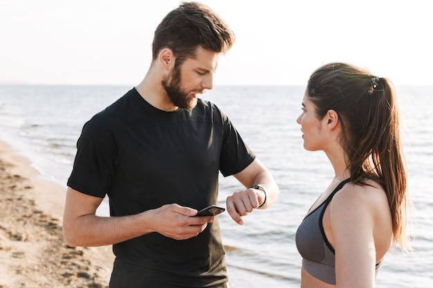 Freudiges junges sportpaar, das smartwatch anpasst