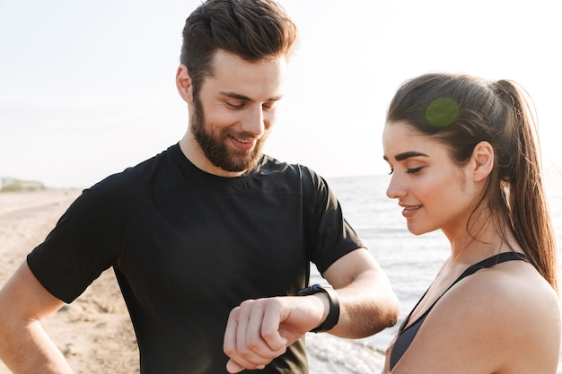 Freudiges junges sportpaar, das smartwatch betrachtet
