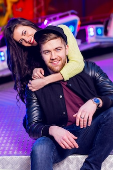 Freudiges junges stilvolles paar, das verspielt ist, während es eine attraktionsparkarkade mit fahrgeschäften besucht
