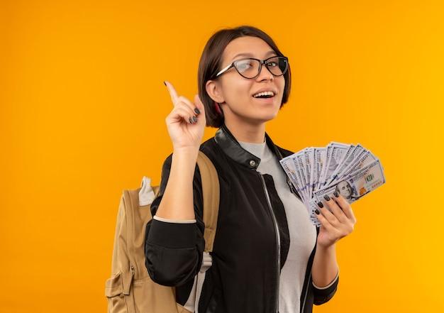 Freudiges junges studentenmädchen, das brille und rückentasche hält, die geld hält und finger lokalisiert auf orange hebt
