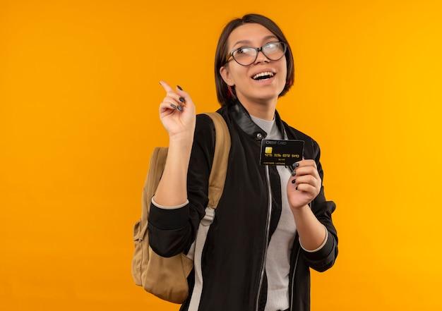 Freudiges junges studentenmädchen, das brille und rückentasche hält, die kreditkarte hält, die seite erhöht finger lokalisiert auf orange