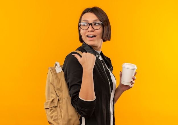 Freudiges junges studentenmädchen, das brille und rückentasche trägt, die in der profilansicht hält, die plastikkaffeetasse zeigt und hinter lokalisiert auf orange schaut