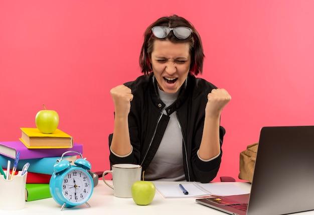 Freudiges junges studentenmädchen, das eine brille auf dem kopf sitzt, der am schreibtisch sitzt und hausaufgaben macht, die fäuste mit geschlossenen augen ballen, die auf rosa lokalisiert werden
