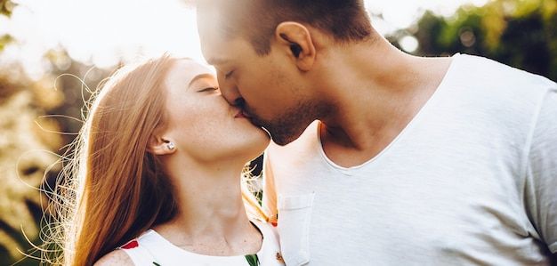 Freudiges kaukasisches paar, das küsst und einen romantischen tag zusammen im park hat