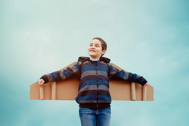 Freudiges kind, das gegen blauen himmelhintergrund spielt. freiheit zu träumen