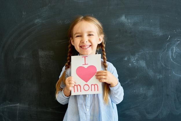 Freudiges kleines mädchen, das grußkarte für mama hält