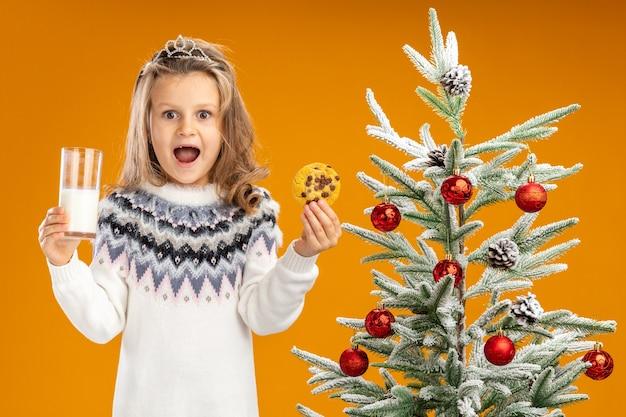 Freudiges kleines mädchen, das nahe weihnachtsbaum steht, der tiara mit girlande am hals hält glas der milch mit keksen lokalisiert auf orangefarbenem hintergrund trägt