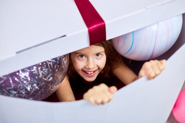 Freudiges kleines mädchen im rosa kleid schaut aus der großen geschenkbox mit luftballons heraus