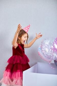 Freudiges kleines mädchen im rosa kleid und im hut öffnet große geschenkbox mit luftballons