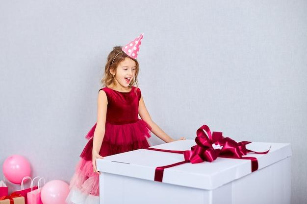Freudiges kleines mädchen im rosa kleid und im hut öffnet große geschenkbox mit luftballons Premium Fotos