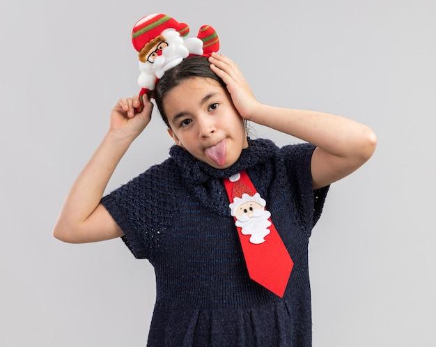 Freudiges kleines mädchen im strickkleid mit roter krawatte mit lustigem weihnachtsrand auf dem kopf, der spaß hat, zunge herauszustecken