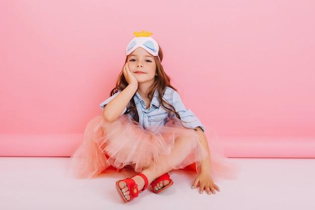 Freudiges kleines mädchen im tüllrock, der auf weißem boden lokalisiert auf rosa hintergrund sitzt. hübsches prinzessinkind mit maske auf dem kopf, das zur kamera lächelt und glück des hübschen kindes ausdrückt