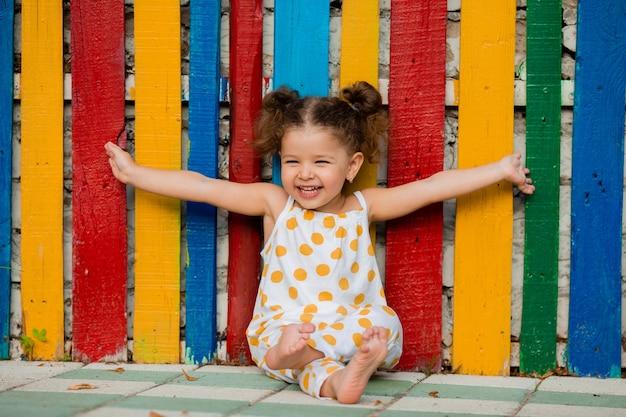 Freudiges kleines mädchen mit offenen händen lacht und schickt allen liebe. hinter ihr befindet sich ein mehrfarbiger holzzaun