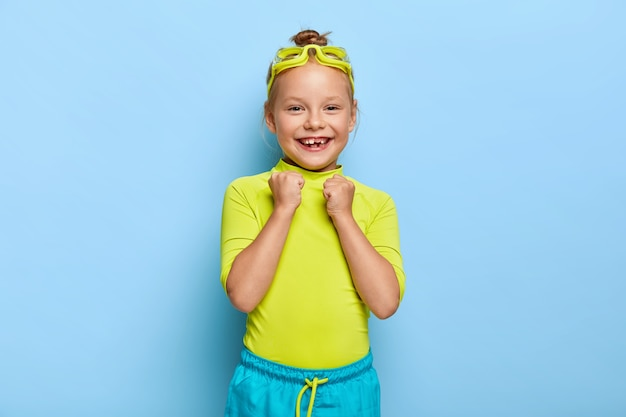 Freudiges kleines weibliches kind hebt geballte fäuste, freut sich über erfolgreiches schwimmen, trägt eine schutzbrille, helle kleidung, hat ein zahniges lächeln, genießt ihr lieblingshobby während der sommerferien. glückliche kindheit