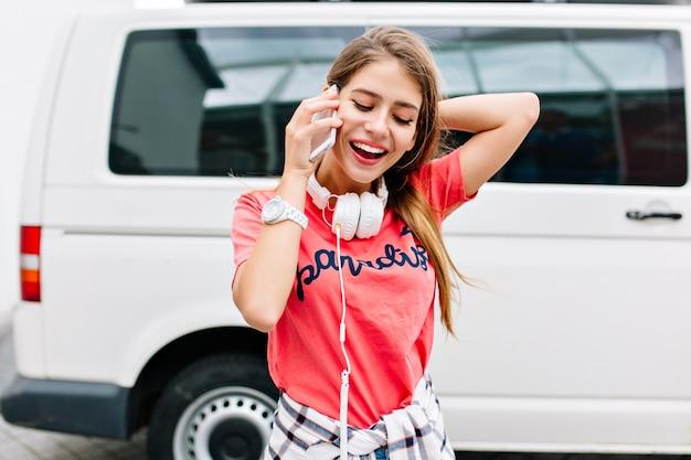 Freudiges lächelndes mädchen im trendigen rosa hemd, das lieblingsmusik genießt, die nahe weißem auto steht