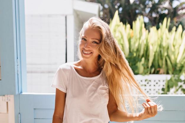 Freudiges leicht gebräuntes mädchen mit aufrichtigem lächeln, das aufwirft. anmutige kaukasische frau, die ihre blonden haare hält.