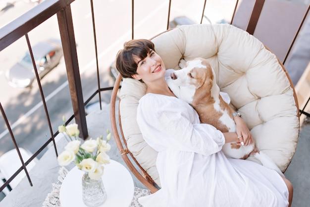 Freudiges mädchen, das im stuhl neben vase der weißen rosen und des streichelnden beagle-hundes sitzt. schöne braunhaarige frau, die frische luft auf balkon mit haustierlügen auf ihren knien genießt