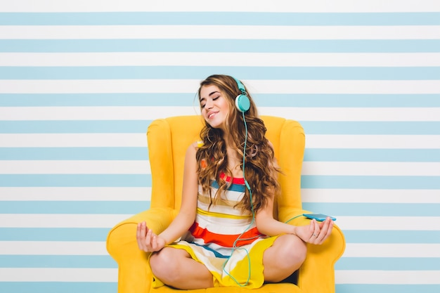 Freudiges mädchen, das meditiert, während es in einer lotushaltung auf blau gestreifter wand sitzt. hübsche junge frau im bunten kleid, das im gelben sessel chillt und entspannende musik hört.