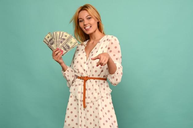 Freudiges mädchen gewann die lotterie und hält einen fan von us-dollar in ihren händen auf einem blauen hintergrund