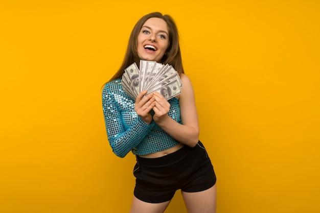 Freudiges mädchen gewann die lotterie und hält einen fan von us-dollar in ihren händen auf einem gelben hintergrund