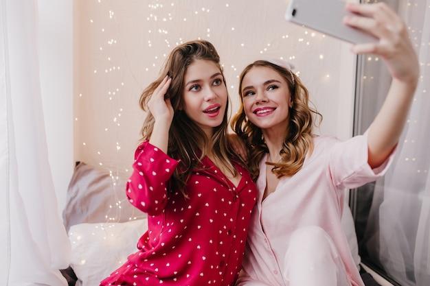 Freudiges mädchen im roten pyjama, das ihr haar berührt, während sie in ihrem zimmer aufwirft. innenfoto von lustigen damen in nachtanzügen, die selfie mit telefon machen.