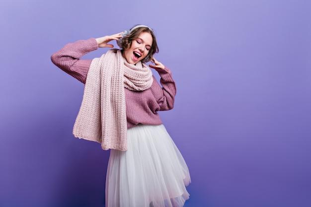 Freudiges mädchen im üppigen weißen rock, der unten mit inspiriertem lächeln schaut. raffinierte brünette dame im langen warmen schal verträumt, das auf lila wand aufwirft.