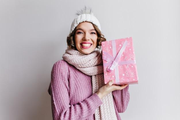 Freudiges mädchen in der strickmütze und im schal, die rosa schachtel mit band halten. glückliche junge kurzhaarige frau mit neujahrsgeschenk, das mit lächeln auf weißer wand aufwirft.