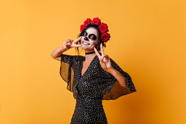 Freudiges mädchen in hochstimmung für halloween posiert in der orangefarbenen wand und zeigt friedenszeichen. porträt der frau im schwarzen kleid niedlich lächelnd