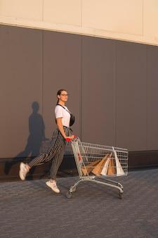 Freudiges mädchen mit dem einkaufen außerhalb eines einkaufszentrums
