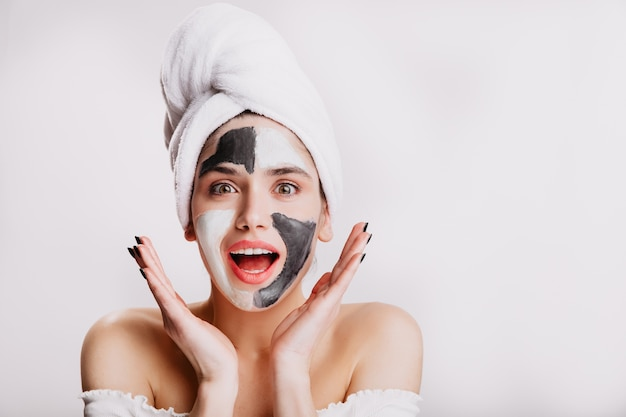 Freudiges mädchen mit gesichtsmaske in überraschung. grünäugige frau posiert auf weißer wand, nachdem sie ihre haare gewaschen hat.