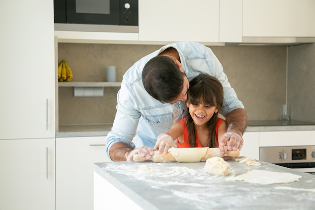 Freudiges mädchen und ihr vater, die spaß in der küche haben, während teig rollen und kneten.