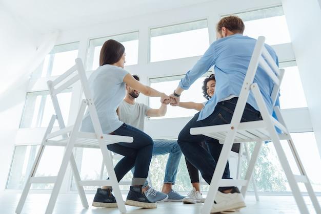 Freudiges, nettes, enthusiastisches team, das zusammen im kreis sitzt und seine einheit zeigt, während es bereit ist, zusammenzuarbeiten