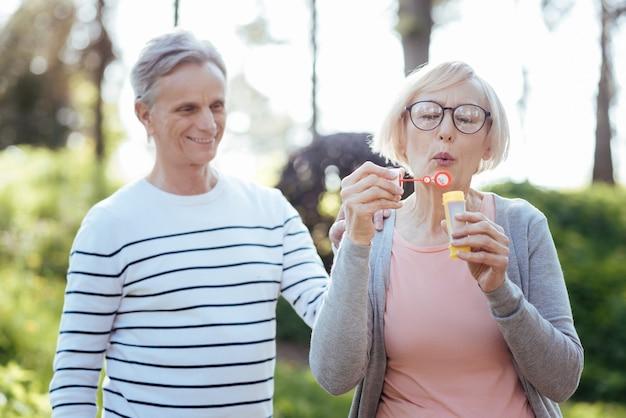 Freudiges, optimistisches paar im ruhestand, das seifenblasen macht, während es das wetter im park genießt und sein glück ausdrückt