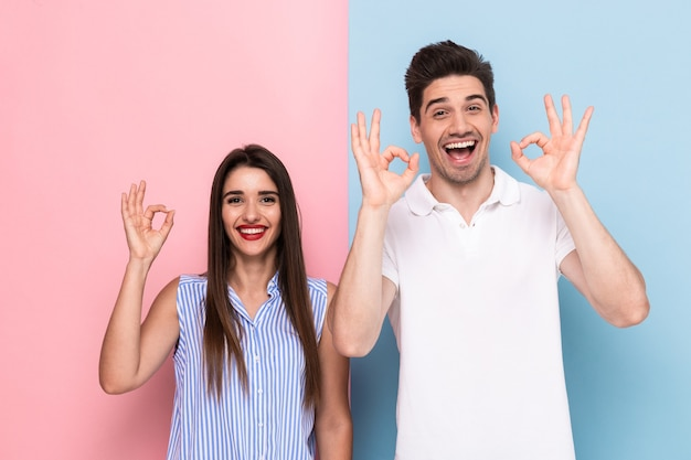 Freudiges paar in der freizeitkleidung lächelnd und gestikulierendes ok zeichen, lokalisiert über bunte wand