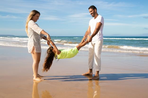 Freudiges paar und kleines mädchen, das spaß am strand hat, eltern, die mädchen arme und beine halten und sie schaukeln