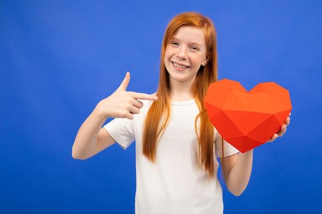 Freudiges rothaariges junges mädchen, das ein rotes herz aus papierblau mit kopienraum hält