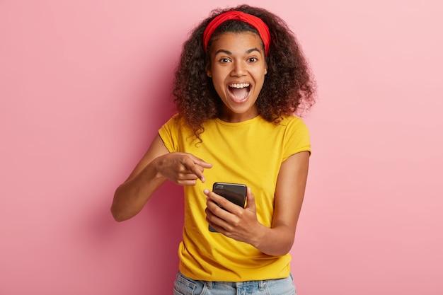 Freudiges schönes junges mädchen mit lockigem haar, das im gelben t-shirt aufwirft
