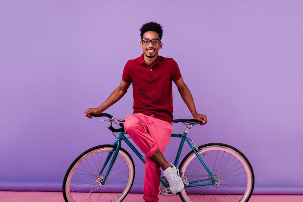 Freudiges schwarzes männliches modell in der rosa hose, die auf fahrrad sitzt. innenaufnahme des lachenden afrikanischen jungen in den gläsern lokalisiert.