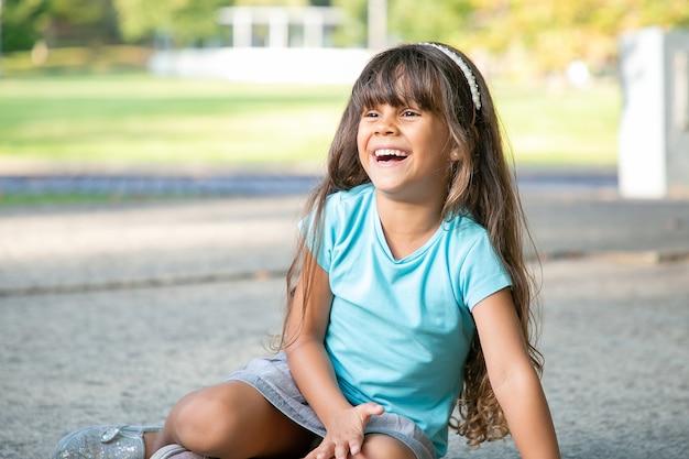 Freudiges süßes schwarzhaariges mädchen, das auf boden sitzt, wegschaut und lacht. konzept für kindheit und outdoor-aktivitäten
