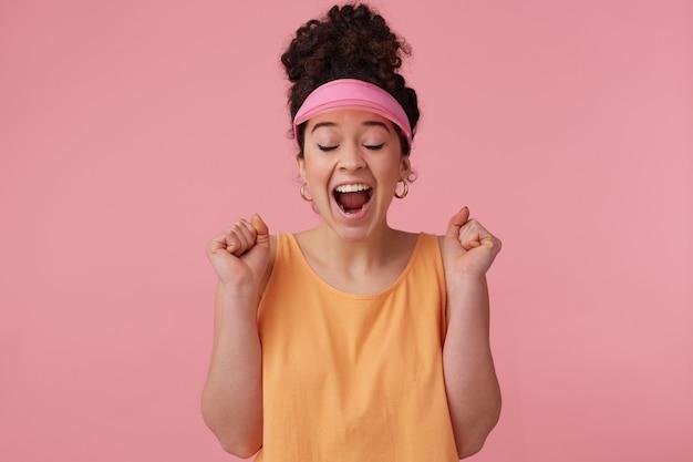 Freudiges, überraschtes mädchen mit dunklem lockigem haarknoten. tragen sie ein rosa visier, ohrringe und ein orangefarbenes trägershirt. hat sich geschminkt. ballen sie die fäuste zusammen und schließen sie vor aufregung die augen