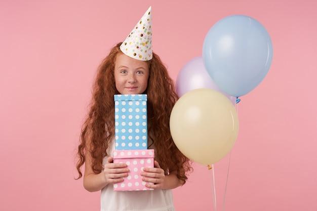 Freudiges weibliches rothaariges kind, das geschenkverpackungen hält und überrascht ist, viele geburtstagsgeschenke zu erhalten, gekleidet in festliche kleidung, in hochstimmung. kinder- und feierkonzept