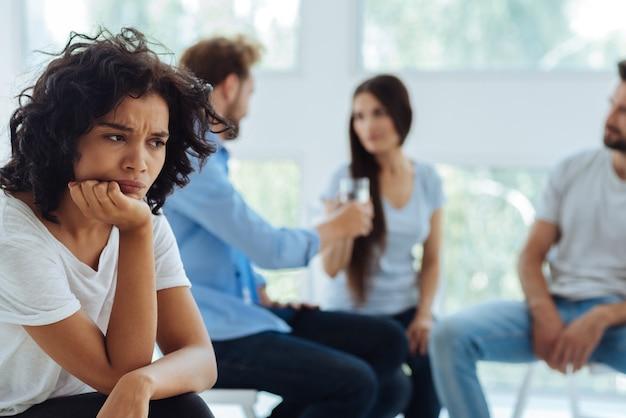Freudlose, nachdenkliche, unglückliche frau, die ihr kinn hält und über eine lösung für ihr problem nachdenkt, während sie gestresst ist